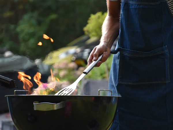 Man barbecuing outside in order to make his house cooler