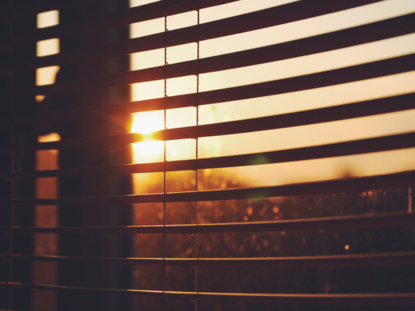 View of sun shining through blinds, keeping house cool